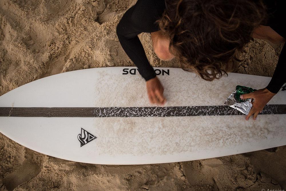 fish waxing surfboard